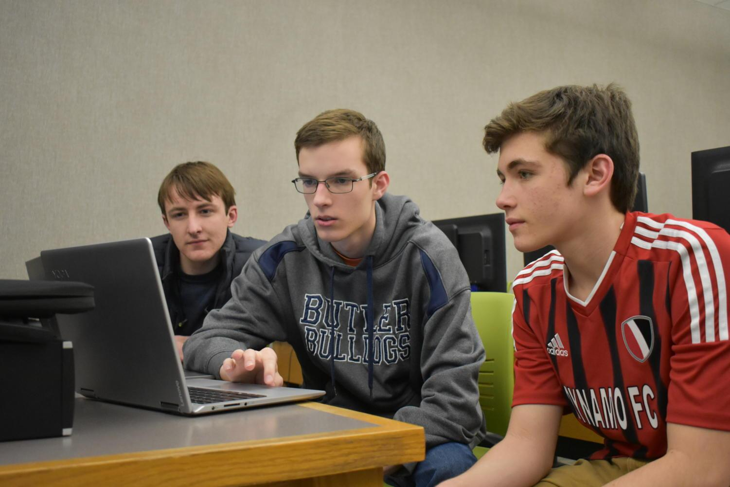 Jared Stigter (center),  Code For Change Technology Lead and junior, helps Xavier Miller (left) and Sam Fang (right), club members and juniors, design a pricing page for the website.