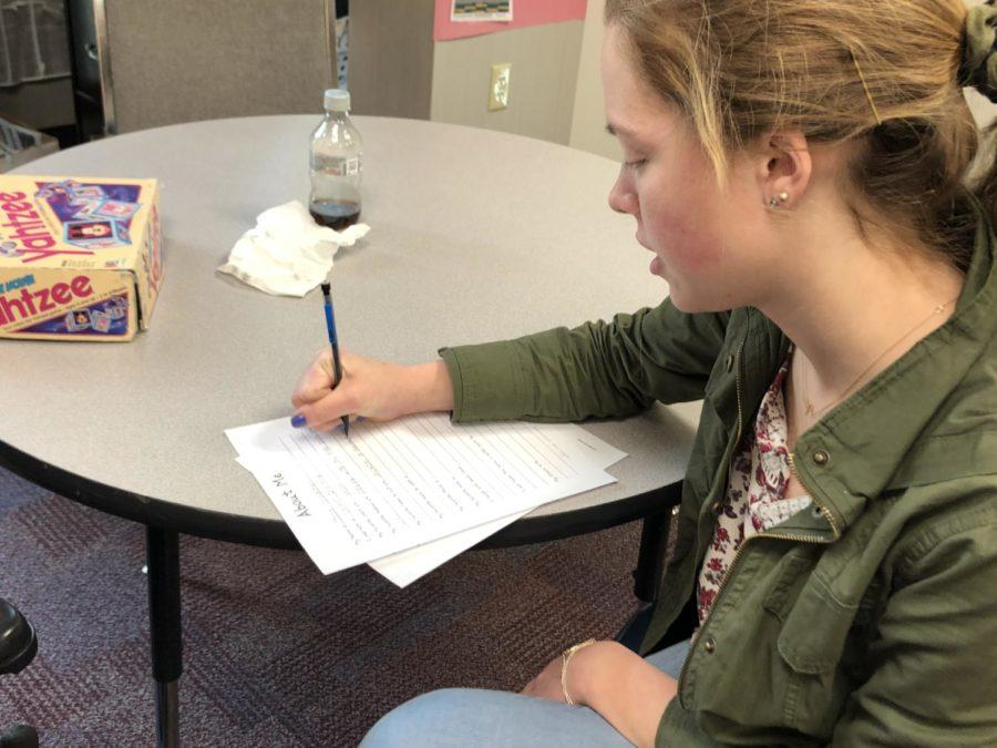 "Anne Schuh, Best Buddies club president and senior, fills out a worksheet for one of the buddies's speech classes. Schuh said, ""It's March— Disability Awareness Month so just getting the message of Best Buddies and inclusion, just spreading that message same as last year."""