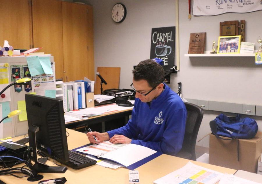 Before school, DECA advisor Richard Reid looks over an ICDC competitor's written paper. Reid said he often ends up spending more time on the papers than role-plays before DECA competitions.