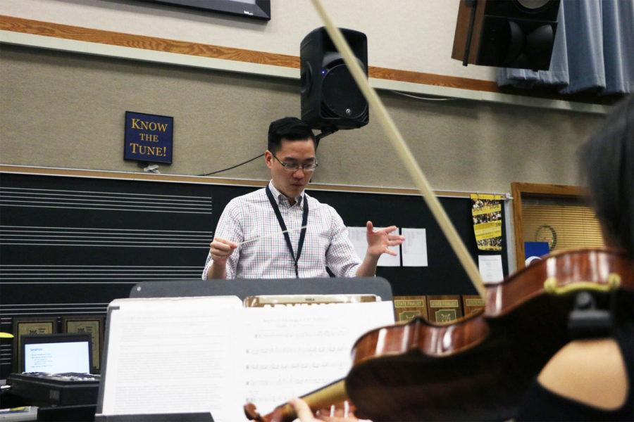 Tom Chen, assistant director of orchestras, conducts the string section of Symphony orchestra during an after school rehearsal. With a little less than a month left to go, the orchestra has been practicing non-stop to prepare for performing in Florida.