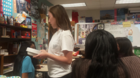 Former president and senior Alexis O'Brien hands out plates during a French Club meeting. She said she was too busy to fulfill her role as French Club president, leaving senior Kelly Xiang to fill her place.