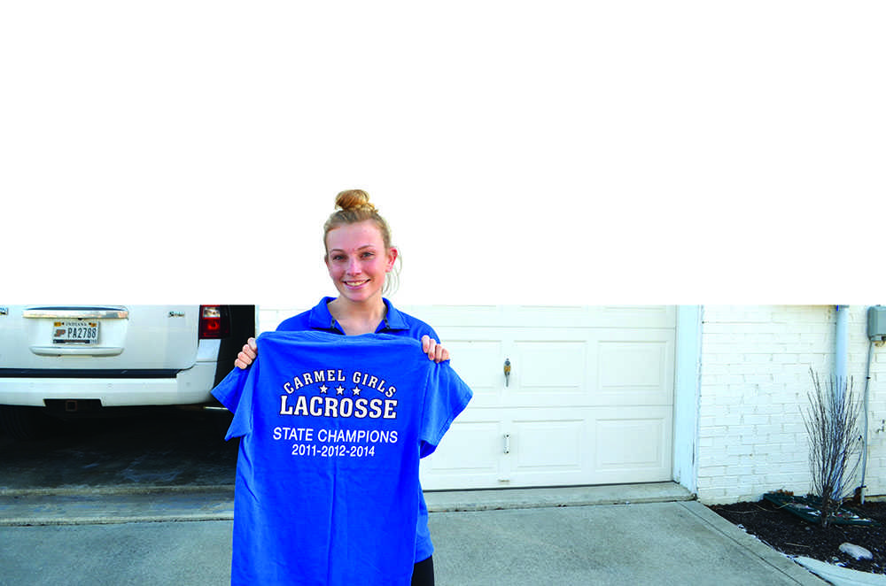CLUB CHAMPION: Senior Ally Hull displays her state champion lacrosse shirt for Carmel Dads Club. Hull has many Dads Club trophies of other sports, such as soccer. Sam Shi | Photo