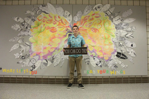 """Senior Eli Lucas stands in front of a colorful angel wing mural in the freshman center. He said being accepted as transgender was very uplifting. A YouTuber himself, Lucas said watching other transgender YouTubers gives him an """"If he can do it, so can I"""" attitude."""