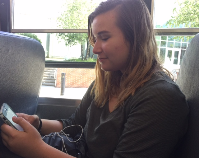 """While riding the bus, junior Mahan """"Mae"""" Ban checks her phone for updates she may have missed during the school day. Ban said that the events the PTO puts on throughout the school year help in establishing school spirit."""