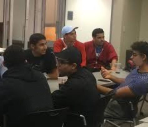 """Ismail Aqeel, club officer and junior (back row, middle), talks with friends during some downtime at school. Aqeel said that he planned to have the MSA host dinners for both Ramadan and for the end of the school year, in an act of celebration. """"I'm not sure when, however, I'm hoping to get something like that done,"""" he said."""