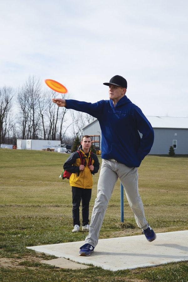 POINTED AHEAD: Junior Seth McLean throws a disc golf disc toward the basket. There are several different types of throws a disc golfer can use.  Veronica Teeter | Photo