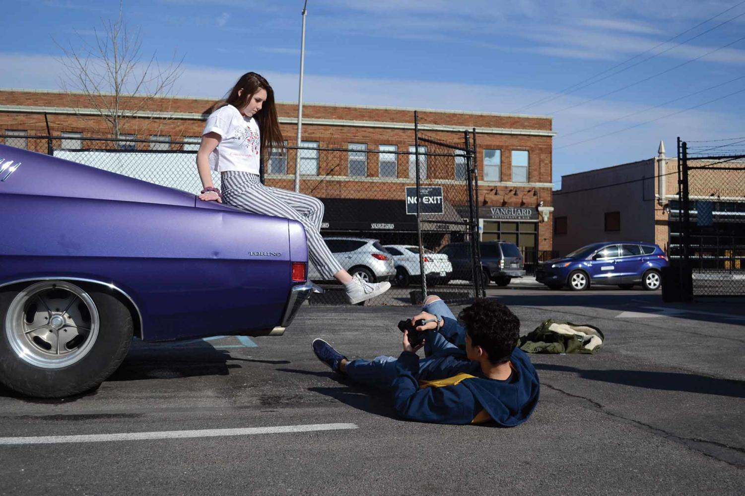 Sophomore Ayman Bolad takes a photo of sophomore Maclean Wood on a retro car. Bolad contacted Wood to collaborate on setting up the outdoor photo shoot.