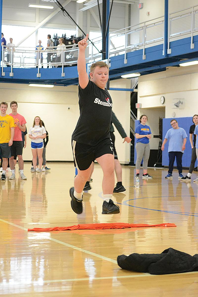 Connor Weindorf, Unified Track member and junior, does a victory jump after completing an event at practice. According to Halle Throgmorton, Unified Track helper and junior, Unified Track provides a fun and competitive environment for participants.