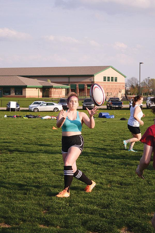 Maddie Schultz, rugby player and junior, catches the ball during a drill. Practices are held at Monon Trail Elementary School.