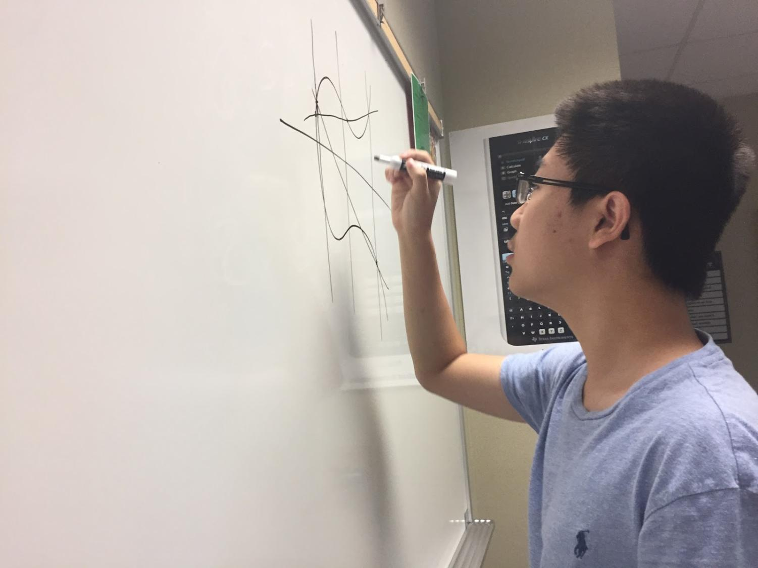 Co-president and senior Kevin Liu finds different approaches to solve a difficult math problem. The members talked about this problem throughout the club meeting.