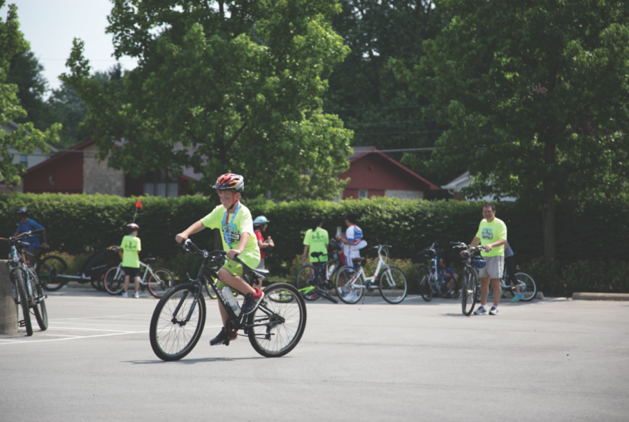 A Bike Carmel participant rides out of a parking lot. Ellie Dyas, avid biker and junior, says that biking helps bring people together.