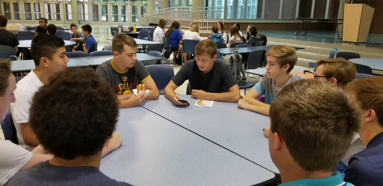 Thomas Gastineau, student leader and senior, leads a group in reading verses in the Bible. CRU Club sponsors decided to have club meetings more student run this year.