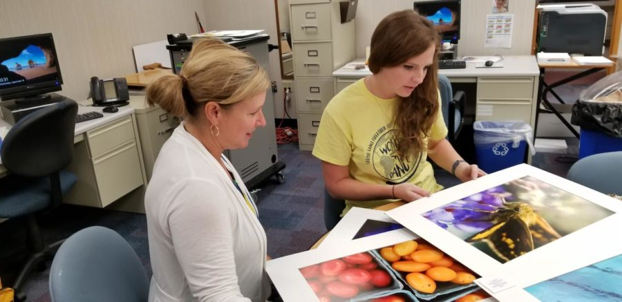 Jen Bubp, co-sponsor of CRU Club(left) and Nicole Palmer(right) look at a piece of art. See You At The Pole will take place on Sept. 26 before school at the flagpole.