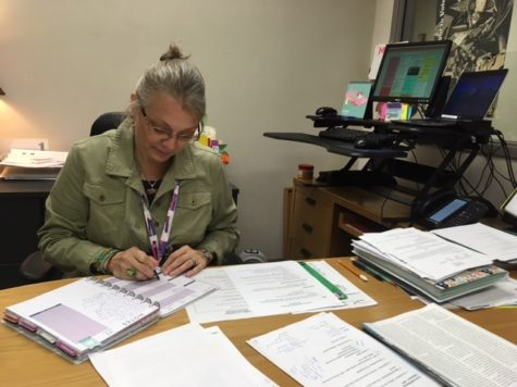 "Terri Ramos, department chairperson for media and communications, looks through her calendar of events. ""The media center is always busy,"" Ramos said. ""We have to stay organized and be on top of things."