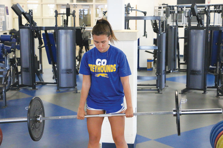 """Apc Work Ethic : CHS soccer player and senior Kate Donovan prepareas to power clean 65 pounds in APC. Donovan has been a varsity soccer player since she was a freshman. """"APC helps me strengthen my arms and leg."""" Donovan said."""