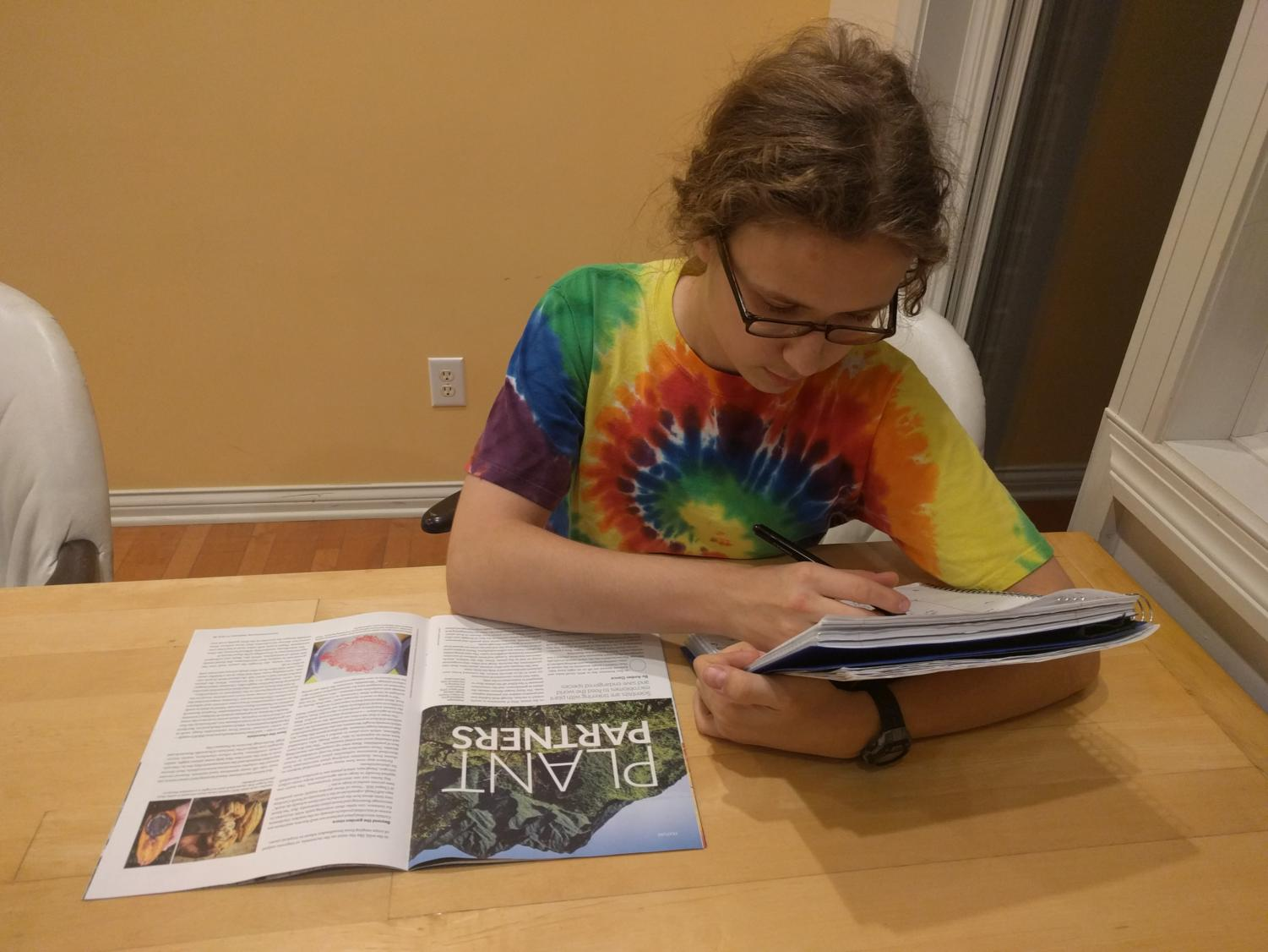 Kian Robinson, club member and junior, reads an article in a magazine about green initiatives.