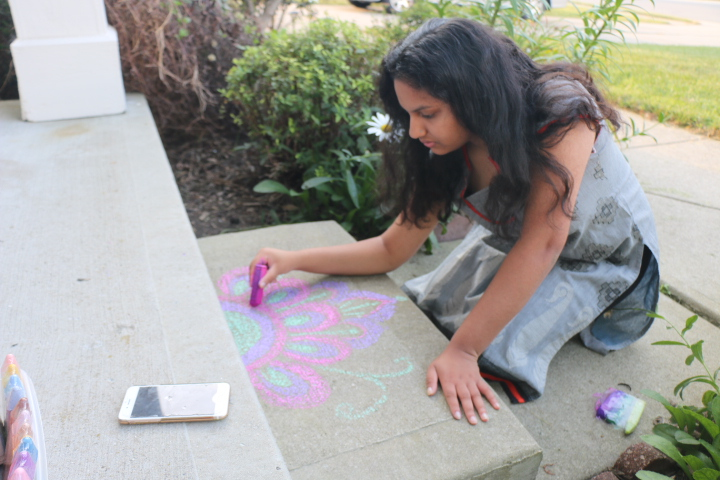 Junior Neharika Palivela draws a rangoli on her front stairs. Rangoli, a folk art from India, is made with chalk,  colored rice, dried flour, or flower petals.