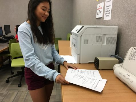 "Annie Kim, officer of the Share the Music and sophomore, stacks flyers for the Share the Music call-out meeting on Sept. 4. Kim had been working to make and print the flyers to provide new members with more information about the club. Kim said, ""It's just a really chill club, and everybody's having a good time."""