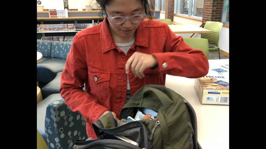 Selin Oh, Camerata cellist and senior, packs up her backpack to leave for orchestra class. Oh said she is especially excited to be playing Dvorak's Symphony No. 9 this entire semester.
