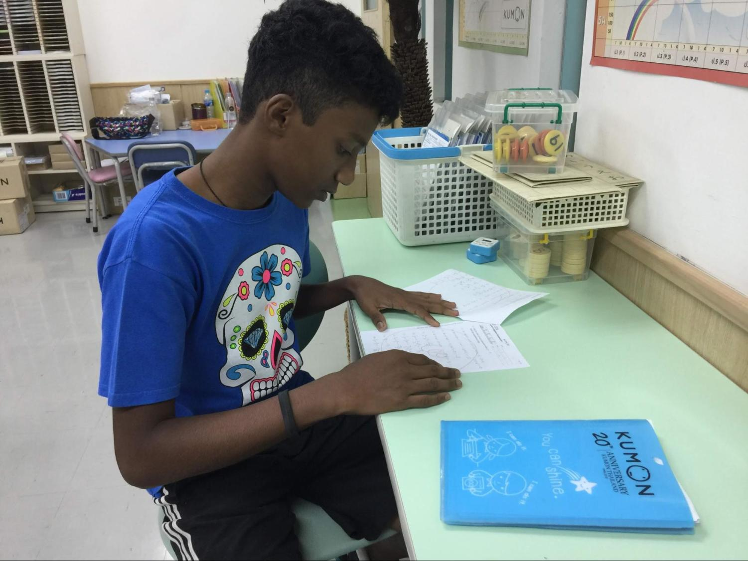 """Vedanth Devadiga, 13, works on his math homework after school at his math tutoring center. """"I really enjoy doing sports with my friends, but I also have a lot of school things on my hands as well."""""""