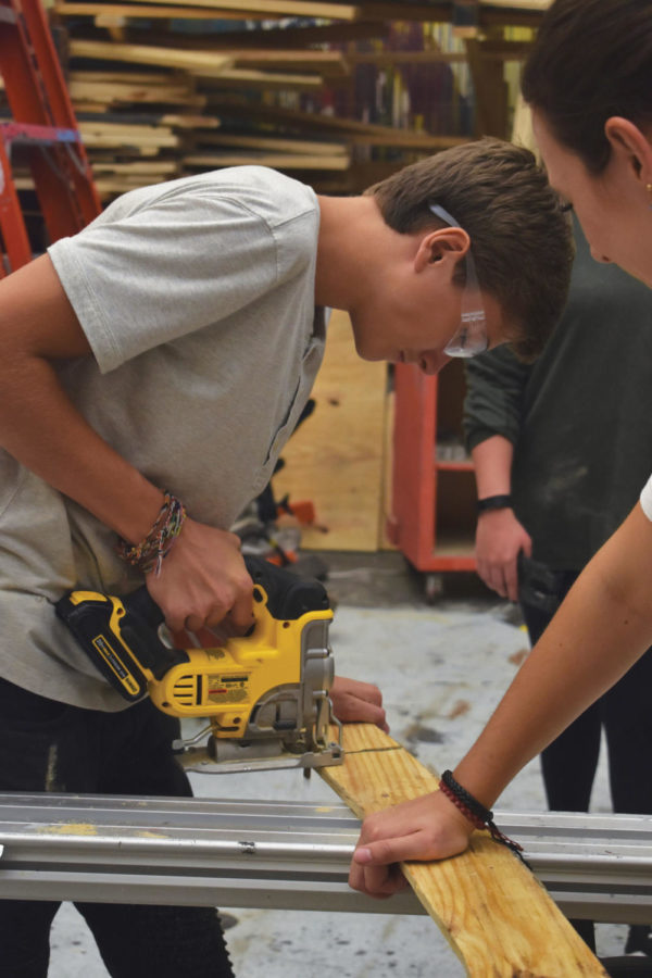 Sophomore+Zachary+Waters+uses+a+panel+saw+to+cut+a+thin+strip+of+wood.+Waters+said+the+class+is+very+hands-on+and+interactive.