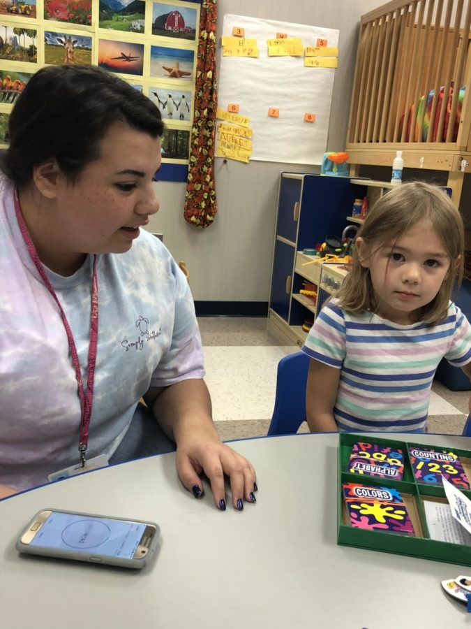 Senior Alissa Bandejas teaches preschooler Breann the instructions to a colors and numbers board game during Kid's Corner preschool on Sept. 10.