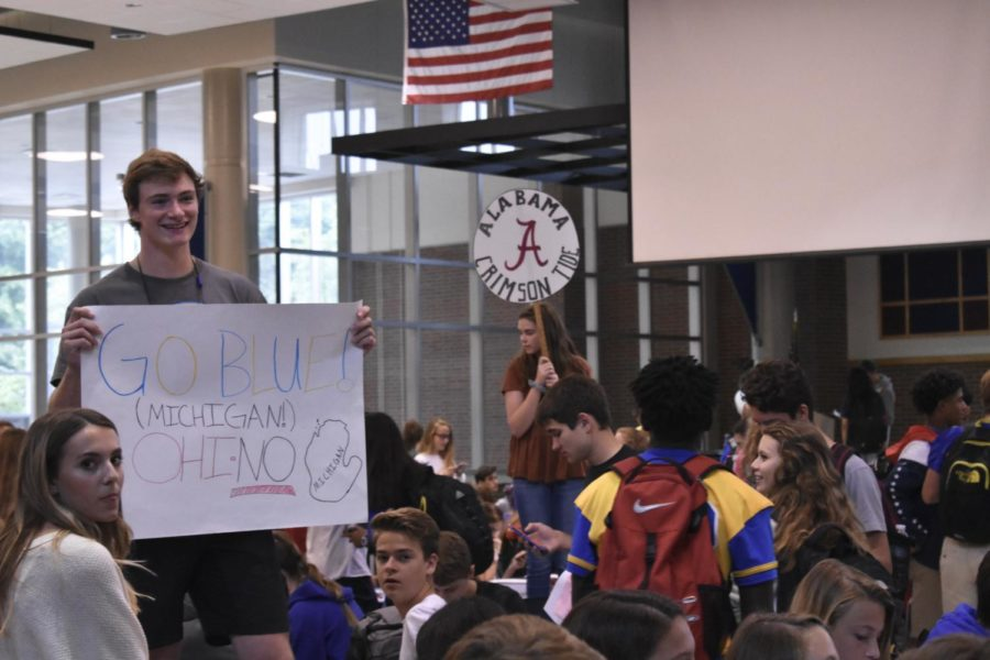 Dawson Cockerham, Cabinet member and senior, raises his House group sign at the first House meeting on September 7. According to Wolff, at the next meeting on Oct. 10, House members will brainstorm activities and themes for Trick-or-Treat for Riley.