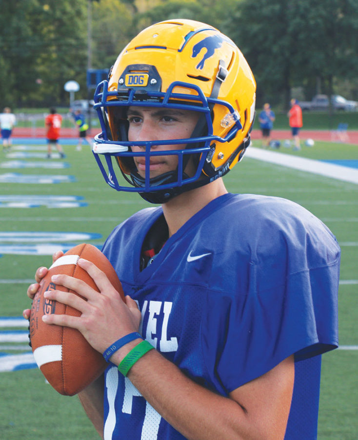 """The Right Mindset: Gabe Quigley, football player and junior, holds a football in """"athletic stance."""" The team's jerseys have a Nike symbol on the left hand corner."""
