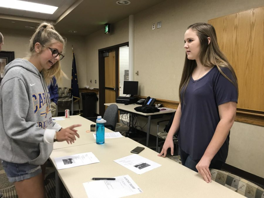 Emily Elzinga, Champions Together co-president and senior, talks to member and senior Bailey Inglis about the upcoming bocce tournament on Oct. 20. Elzinga said the club is trying to get more athletes for the tournament because they only have 12 at the moment.