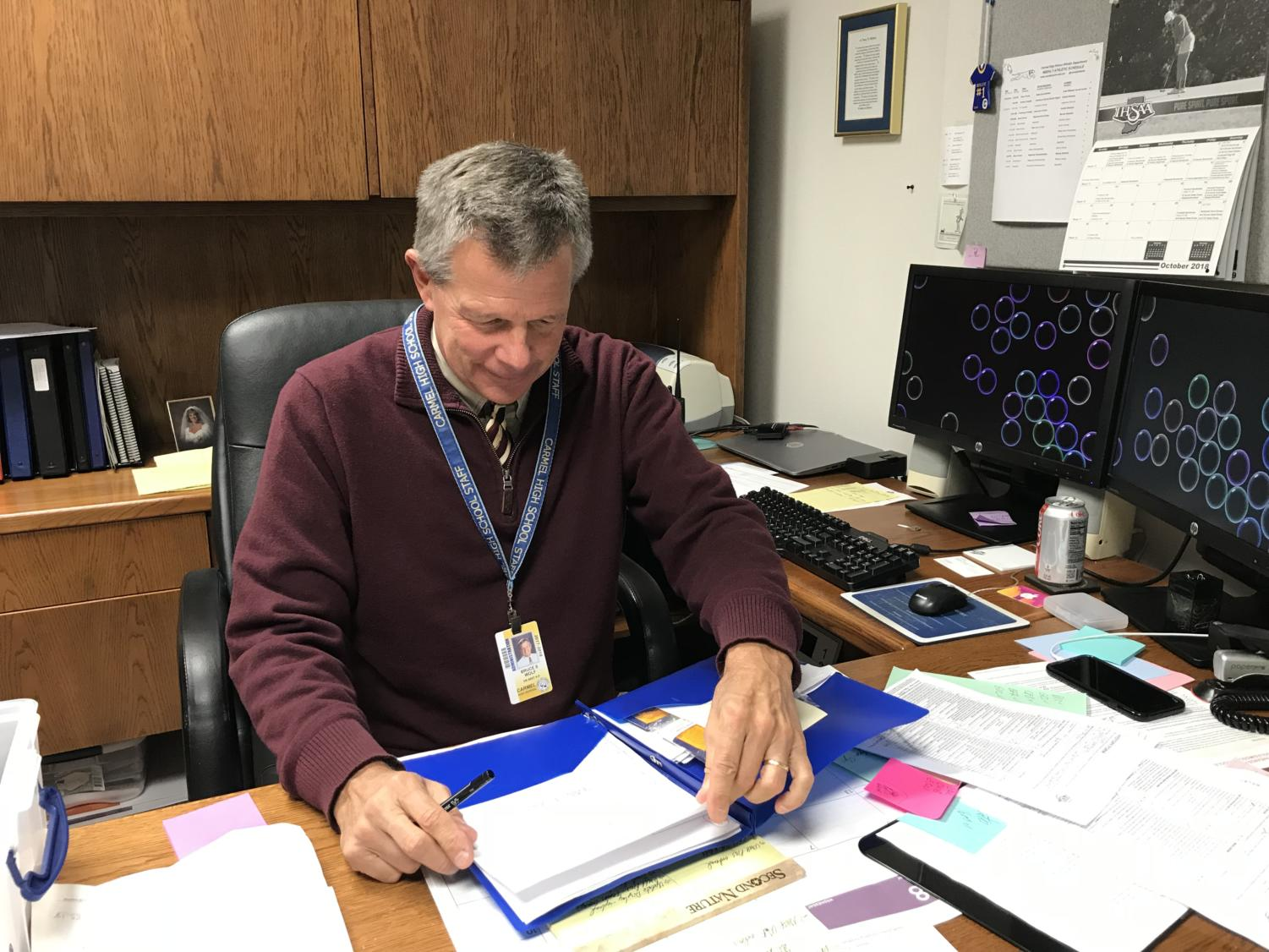 Champions Together co-sponsor Bruce Wolf flips through athletic awards. He said,