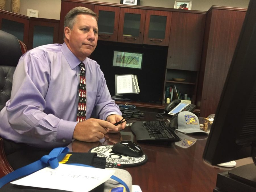 Principal Tom Harmas works at his desk. Harmas said he has recently been developing the Pathways graduation program, new teacher evaluations and teacher professional leave days.
