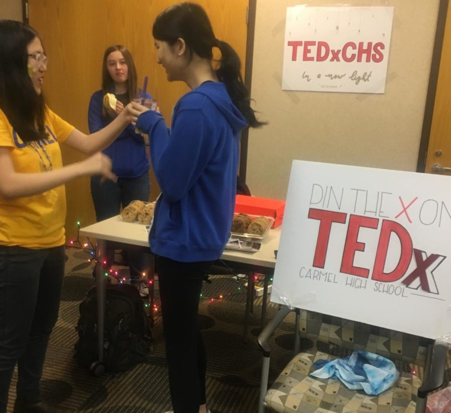 Selin Oh, TEDx president and senior, talks to Sylvia Liu, TEDx Food & Breaks committee head and senior, in front of the TEDx homecoming booth on Sept. 28. Oh said the club has been trying to attract new members this year through its call-out meeting and homecoming booth.