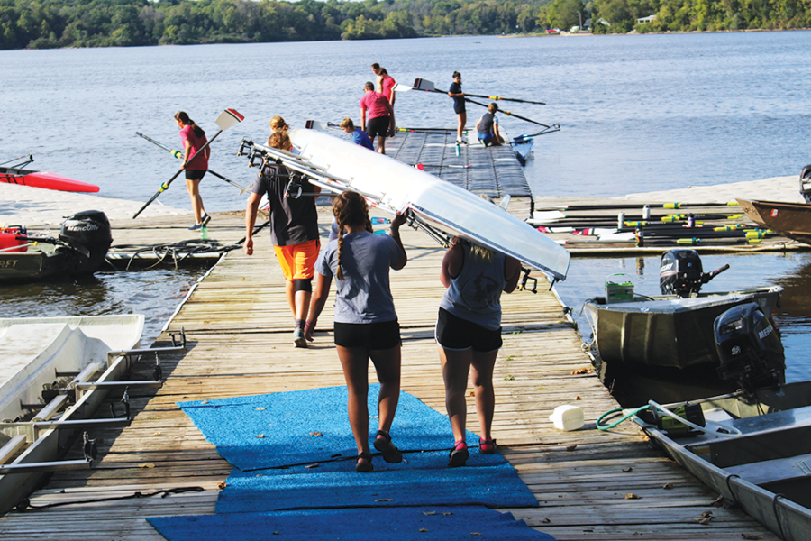 ROWING Hard: Members of the Indianapolis Rowing Center's team (IRC) work to put a boat in the water before practice. The IRC team starts with land training before they get their boats out on the reservoir.