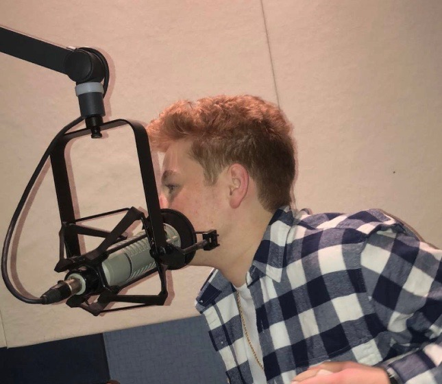 In the recording studio, Spencer Pickering, sports broadcaster and junior, pre-records a segment for the sports section and tests out new equipment.