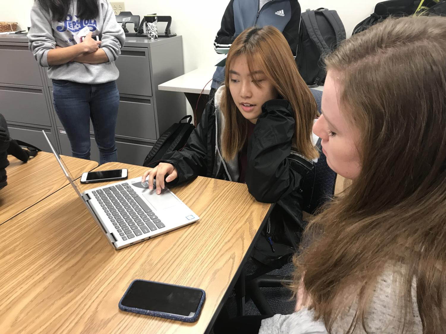 Senior Loraine Lee discusses potential roleplay categories with another DECA member. She said that she wants to help members find a roleplay that interests them because it will help motivate them to practice and do well.