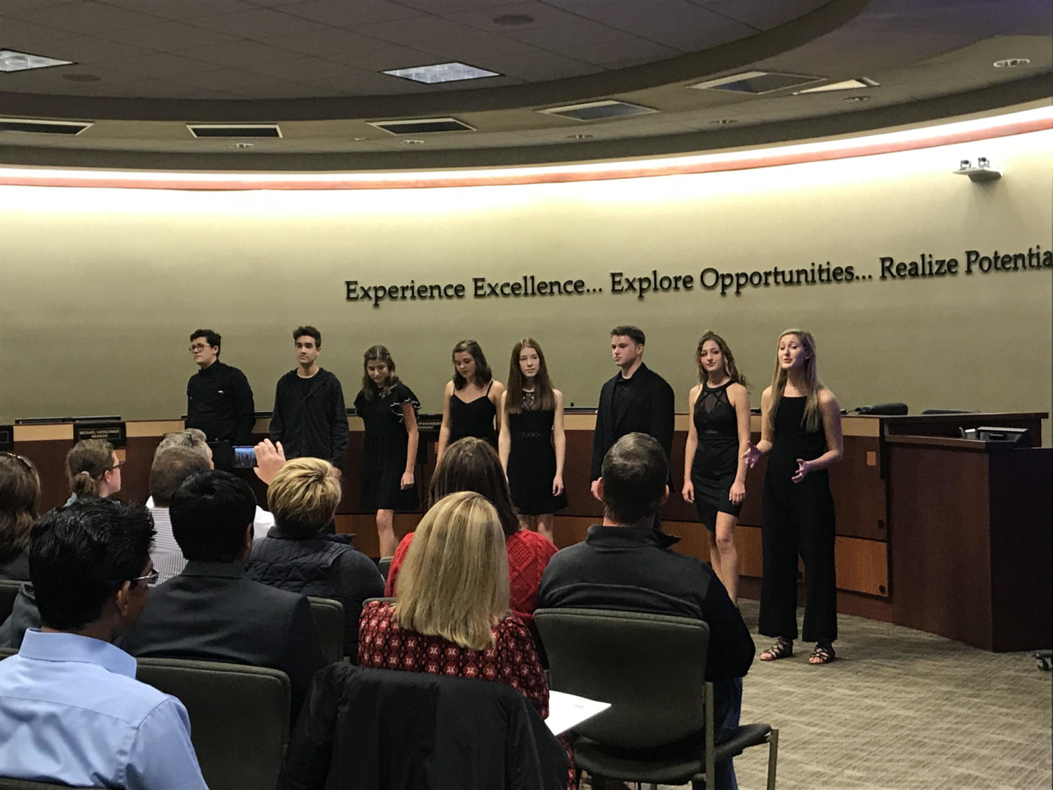 "Choir students perform an excerpt of their musical, ""Edges"", during a school board meeting. During the meeting, the board recognized several outstanding students, including National Merit Semifinalists, the ""Edges"" cast and students with exemplary community service."