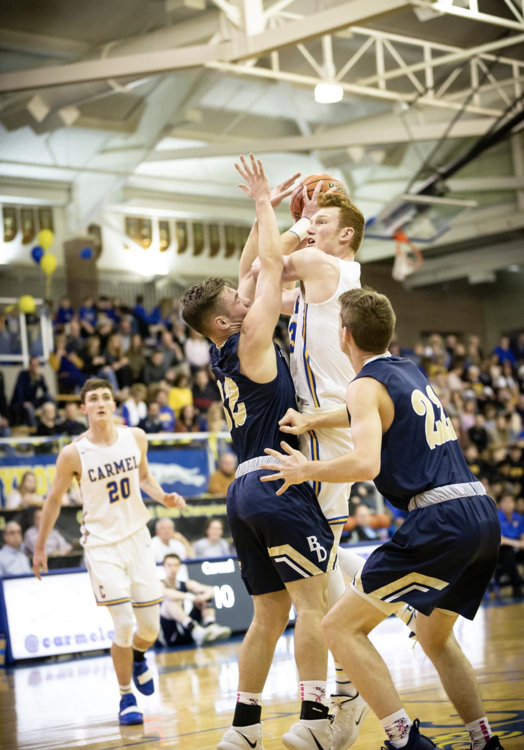A+Foot+Above+The+Rest%3A%0AJohn+Micheal+Mulloy%2C+varsity+basketball+player+and+senior%2C+holds+the+ball+before+attempting+a+layup+during+their+game+against+Fort+Wayne+Dwenger+High+School+on+February+20.+Mulloy+is+the+tallest+student+on+the+Carmel+High+School+basketball+team.+Mulloy+will+be+attending+Butler+University+for+basketball+in+the+fall+of+next+year.+