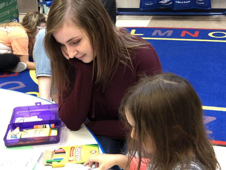 Senior Sophia Long sits with a preschooler as she takes the motor skill test on Nov. 27. This test examines the preschoolers ability to cut paper, draw, and color.