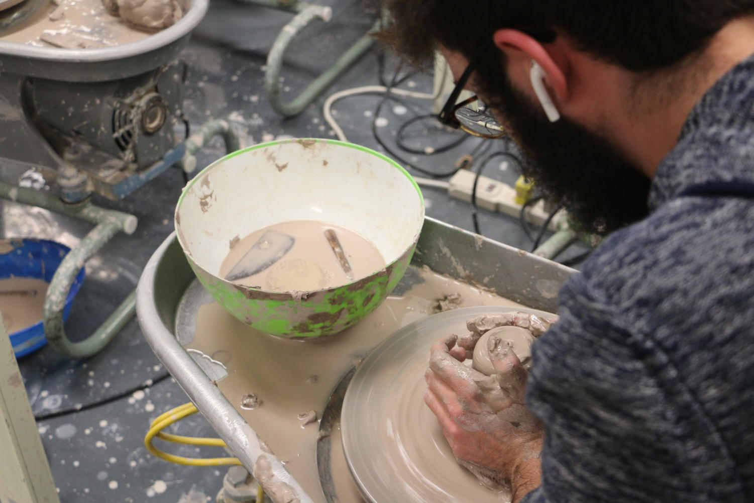 Ceramics+Wheels%3A%0AJunior+Zach+Devore+spins+his+clay+pot+on+the+wheel+in+the+ceramics+4+class+on+March+18.+He+said%2C+%E2%80%9CI+enjoy+this+class+because+it+isn%E2%80%99t+stressful+and+I+can+listen+to+music+while+talking+with+my+friends+too.%E2%80%9D