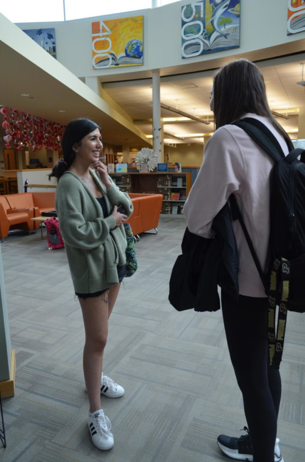Library Discussions: Junior Gabriella Smith converses with her friend during A lunch in the library. Smith was planning her study times for upcoming AP exams.