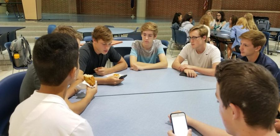 Thomas Gastineau, CRU Club student leader and senior, leads a group in reading verses in the Bible. CRU will host a barn party for all middle and high school students on Nov. 3.