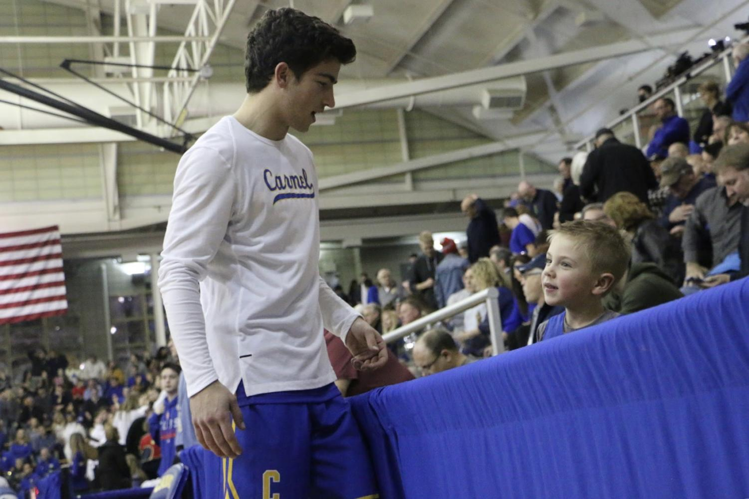 Men%27s+Basketball%3A%0ALucas+%28Luke%29+Heady%2C+men%E2%80%99s+basketball+player+and+senior%2C+chats+with+a+young+fan+prior+to+the+team%E2%80%99s+game+against+Fishers+on+March+1.+The+final+score+was+CHS+62%2C+Fishers+52.