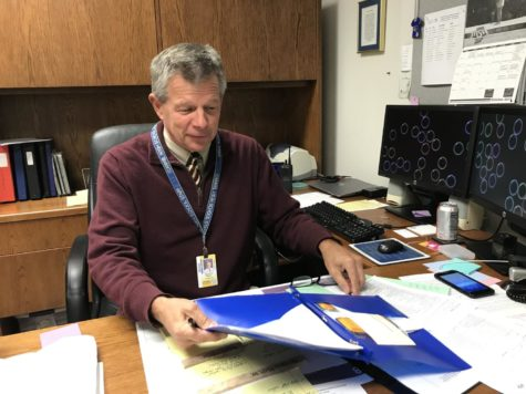 Bruce Wolf, Champions Together co-sponsor and assistant athletic director, reaches for his glasses as he looks through athletic awards. The club will host a Unified Basketball and Cheer Clinic Dec. 7.