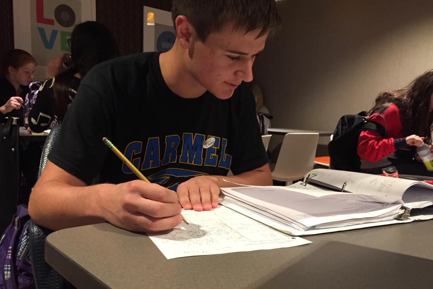 Student body president Tim Metken works on homework in the Carmel Café. Metken said he doesn't think potential plans for a later school start time would be beneficial to students because of extracurricular activities.