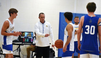 COACHING BOND: Head coach Ryan Osborn giving instructions to the men's basket- ball team during practice. Varsity basketball player and senior Andrew Owens said the relationships between the team and the coaches are stronger due to the program they run building trust between them.