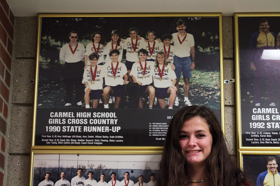 Emma Cappella, sophomore and cross-country runner stands next to a photo of her mother, Allison 'Bailey' Cappella (second on the right, front row). Capella won state runner up in 1990.