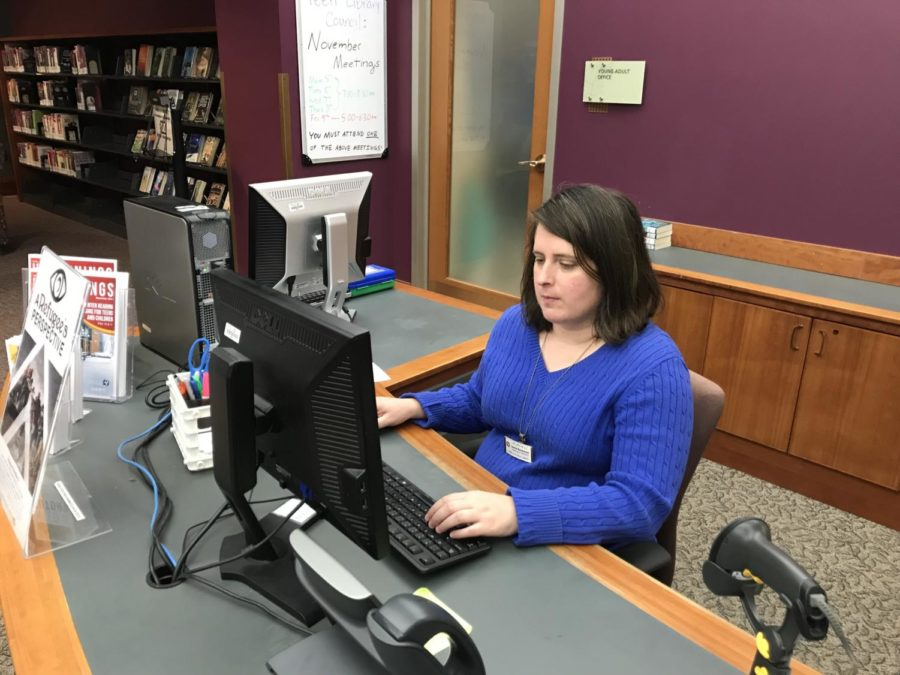 Jamie Beckman, Carmel Clay Public Library young adult librarian, sits at the young adult center desk. Beckman said the library has many November events, including Investigating the Human Body.