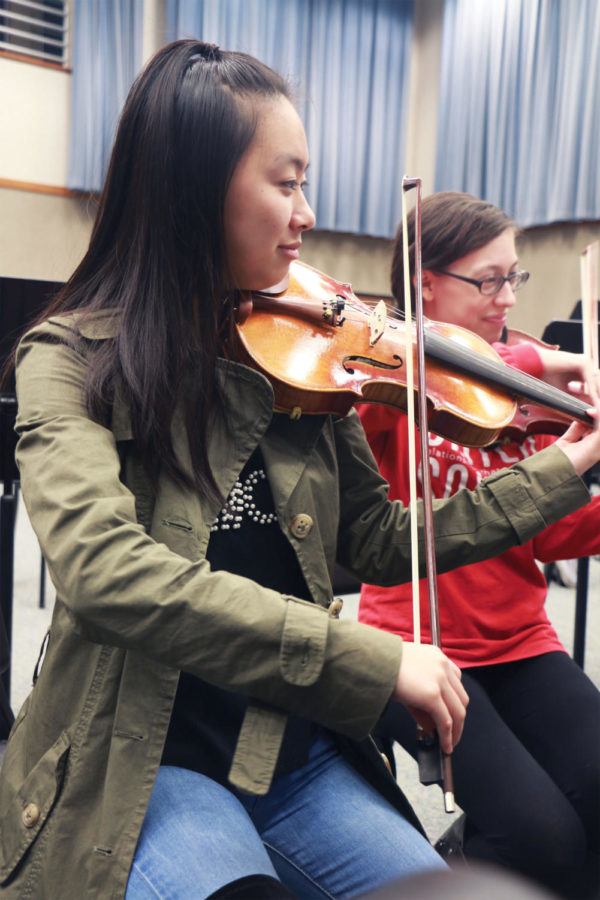 Cynthia Wan, Camerata violinist and junior, practices in class. She said playing with professionals make her look at music differently.