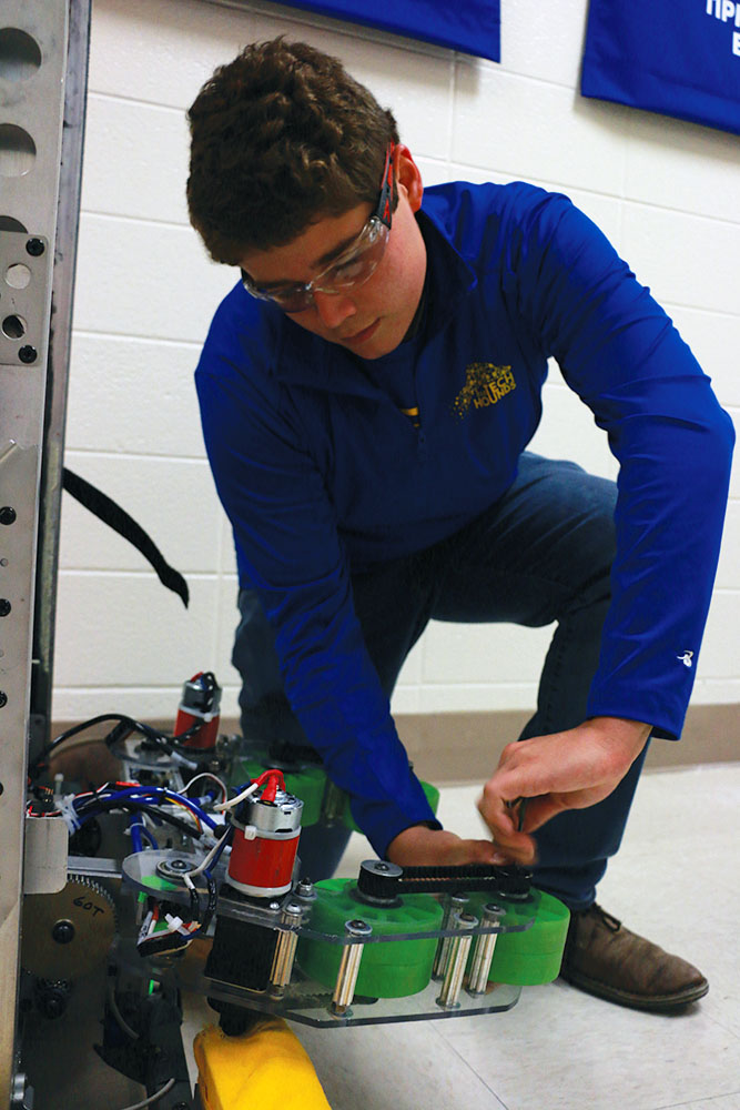 ROBOT MANIA: Derek Fronek, TechHOUNDS Robot Operations Lead and senior, works on intake system for 2018 robot 'Quickdraw.' TechHOUNDS has many aspects to the development of its robots, including programming.