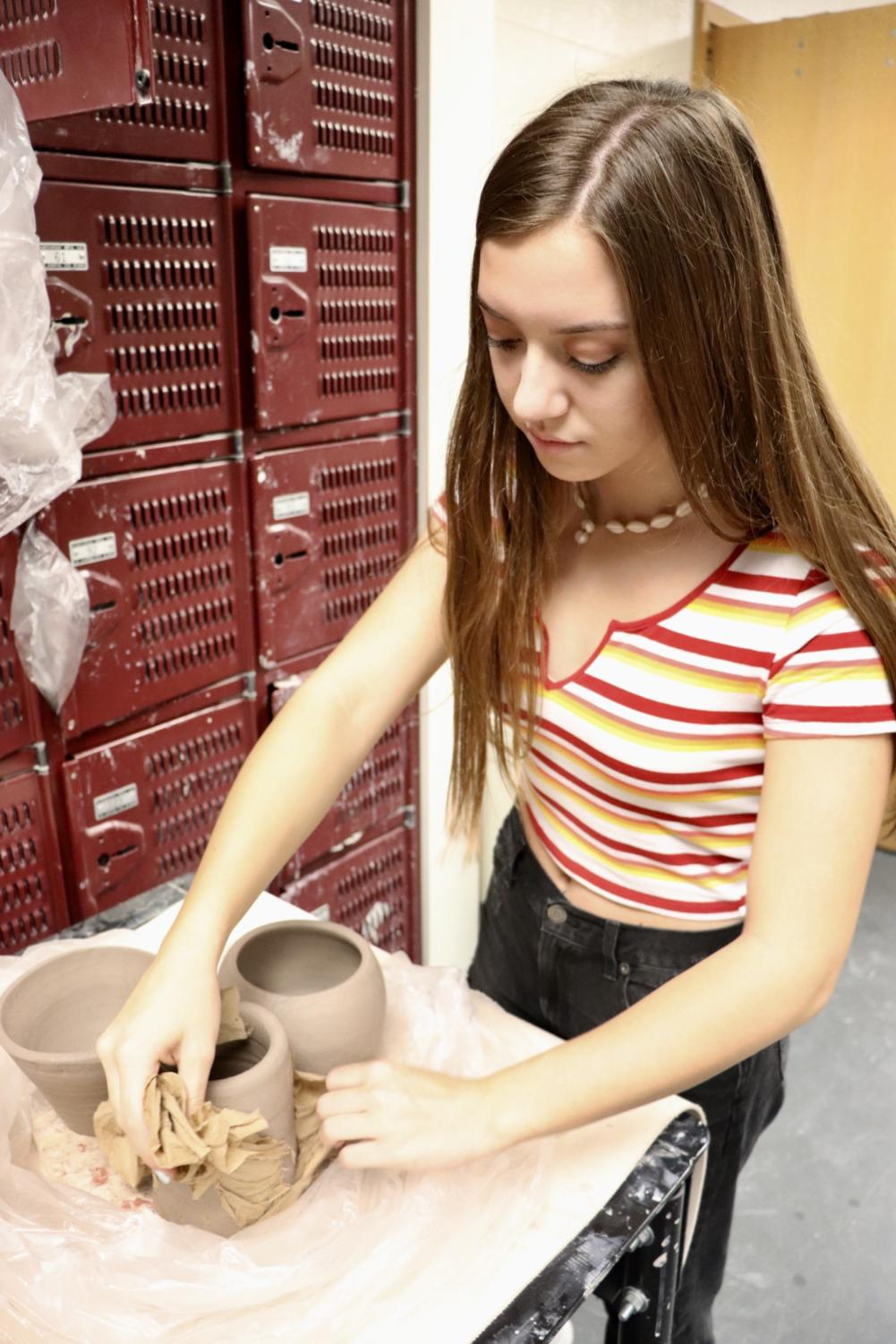 From+Covered+to+Coated%3A+Lilly+Branks%2C+ceramics+student+and+sophomore%2C+unwraps+her+creations+to+reveal+their+bare+clay+outer+shells.+Branks+said+that+the+next+step+in+producing+her+final+product+would+be+coating+the+pieces+with+one+of+the+various+colors+of+glaze.+Some+of+the+colors+used+by+other+students+included+brick+red%2C+light+yellow%2C+and+jade+green.